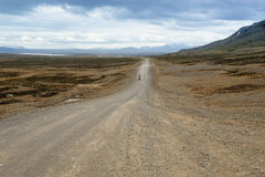By a road in Iceland. A biker traveling on a dirt road of Iceland Royalty Free Stock Photography