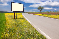 Road through the idyllic scenery and billboard Royalty Free Stock Photo