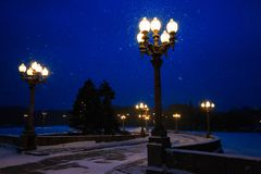 Road illuminated street lights and snowing in winter at night. Royalty Free Stock Photos