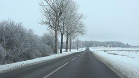 Road inside village covered with white snow after snowstorm. 4K. Road inside a village covered with white snow after snowstorm. Frost and snow covered trees and stock video footage