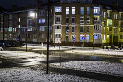 Road intersection on a winter night. And the house with a light in the windows Royalty Free Stock Image