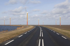 Road on the island of flevoland with wind turbines and blue sky Royalty Free Stock Image