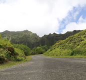 Road and Koolau Mountain Range 2. Road leading into a tropical area with mountains in background with clouds and blue sky Stock Image