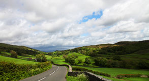 Road in Lake District. Road receding through green countryside of Lake District National Park, Cumbria, England Stock Photo