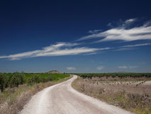 White road. Road in a landscape and sky with clouds stock image
