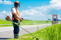 Road landscaper cutting grass. Along the highway using string lawn trimmer stock image