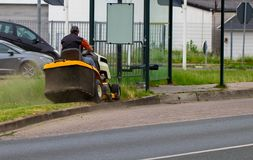 Road landscaper cutting grass along the street.  royalty free stock images