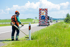 Road landscapers cutting grass around mileposts Stock Photo