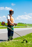 Road landscapers cutting grass using string lawn trimmers stock photos
