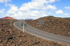 Road through lava rocks and volcanic mountains near Los Hervideros Stock Photos