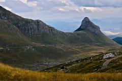 A road leading along a mountain slope under a rocky mountain stock photos