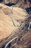 Road leading through dry and cold rough landscape of high Atlas mountains Royalty Free Stock Photo
