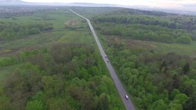 Road leading through forest and village to mountains. Aerial view. Road leading through forest and small village or town to mountains, on road there are vehicles stock footage