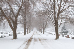Road leading through a graveyard. A snowy road leading through a cemetary in the winter royalty free stock photo