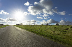 Road leading into the horizon. Sunshine and clouds over the horizon on a green grassy country lane Stock Photos