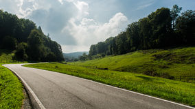 Road leading through landscape. Road leading through green landscape with trees and hills Stock Images