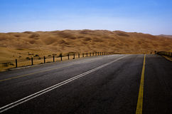 Road leading through sand dunes in the desert of Liwa Oasis United Arab Emirates. Desolate road winding through the sand dunes of Liwa region near Abu Dhabi UAE Stock Photos