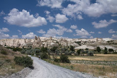 Road leading to beautiful desert rocky sandstone valley with huge troglodytes in blue sky with clouds Stock Images