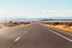 Road leading to distance. A view of a road leading to the distance on a dry grassy plain Stock Images