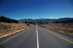 Road Leading To The Drakensberg. A newly tarred road leads away into the mountains away from Underberg towards Sani Pass, KZN, South Africa stock photos