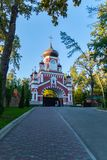The road leading to the entrance with an arch and domes on the territory of the church parish is located behind the. Fence. With tall trees growing there. . For Stock Photos