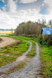 Road Leading To The Fields. A typical field road in the rural Finland. The road is a maintenance route for the farm machinery stock photo