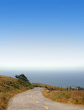 Road Leading to the Ocean. Road winding down to the ocean on a clear, sunny day. Known as California's Lost Coast near Cape Mendocino Royalty Free Stock Image