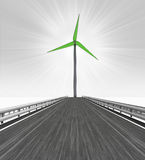 Road leading to one big windmill turbine Stock Photo