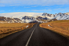 Road leading to snow covered mountains Royalty Free Stock Photo