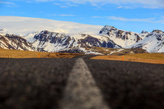 Road leading to snow covered mountains Royalty Free Stock Images