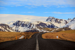 Road leading to snow covered mountains Stock Photography