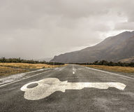 Road leading to success. Natural landscape of asphalt road and drawn key as success symbol Royalty Free Stock Image