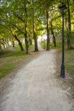 Road leading trough park. Gravel path leading trough city park Stock Photos