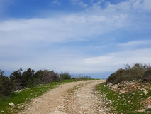 The road leading up into beautiful uncertainty. The road to top of the hill leading up into beautiful uncertainty, national nature park, blue cloudy sky. Concept Royalty Free Stock Image
