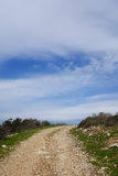 The road leading up into beautiful uncertainty. The road to top of the hill leading up into beautiful uncertainty, national nature park, blue cloudy sky. Concept Royalty Free Stock Photography