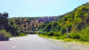 The Road leads in mountains high. The Trip on machine on road in mountains.The Fresh air and beautiful vegetation in mountain high.The Good places for rest and stock footage
