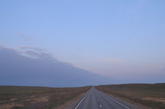 Road leaves for horizon. The steppe around. Stock Photo