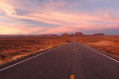 The road led to the Monument Valley. This is probably one of the mostly filmed or photographed road. It's sunrise at the Monument Valley royalty free stock photos