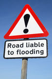 Road liable to flooding. Road liable to flooding warning sign and a blue sky Royalty Free Stock Images