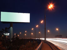 Road with lights and large blank billboard. At dark night in city stock images