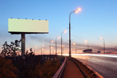 Road with lights and large blank billboard. At evening in city stock image