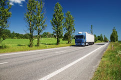 Road lined with poplar alley in the countryside, passing truck Royalty Free Stock Images