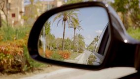 Road lined with tropical palm trees. Reflected in the side view mirror of a motor car stock video footage
