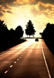 Road with lonely car. Red sunset light and high contrast stock photos