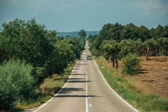 Road with lonely car through rural landscape and trees. Straight long road with lonely car through rural landscape and leafy trees, on sunny day near Castelo royalty free stock photo