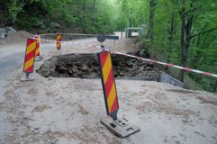 Road Maintenance. Shot of a damaged road segment in the forest Stock Image