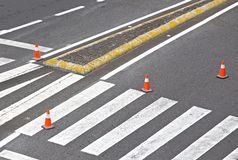 Road just painted with white lines, crosswalk and Striped orange cones. Road maintenance with lines, crosswalk and orange cones royalty free stock photos
