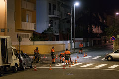 Road maintenance service workers painting zebra at night Stock Photo