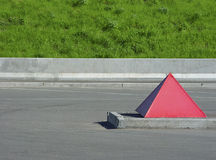 Road mark. The horizontal lines both green grass and one red pyramid are a road in city stock photo
