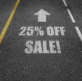 25% off sale road markings. Road marking painted on an asphalt street that says 25% OFF SALE! with an arrow above it pointing forward Royalty Free Stock Photo
